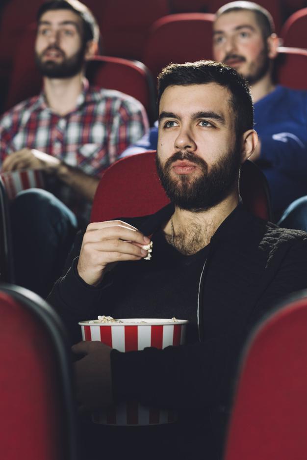 hombre-serio-comiendo-palomitas-maiz-cine_23-2147803797